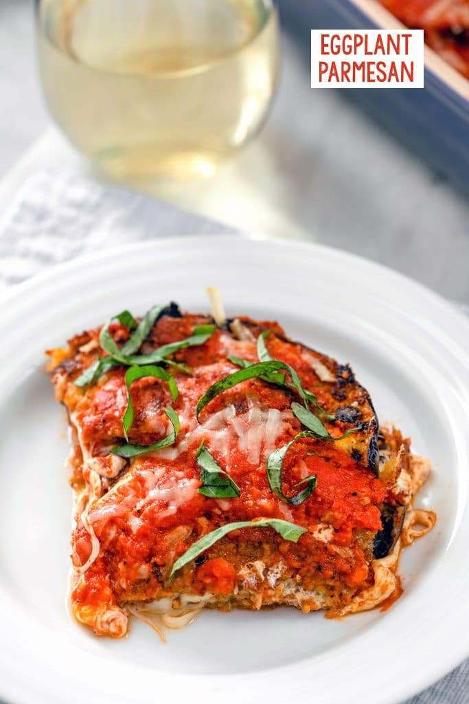 Head-on view of a slice of eggplant parmesan with tomato sauce and basil on a white plate with a glass of white wine in the background and recipe title at top