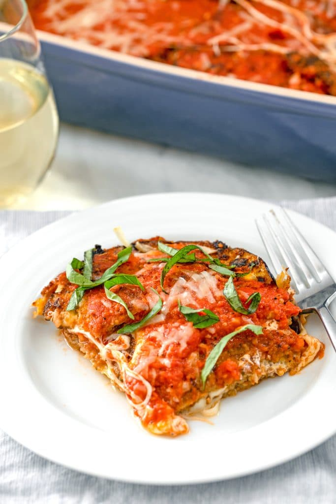 Overhead view of a white plate with slice of eggplant parmesan with fork and a glass of white wine and casserole dish with eggplant parmesan in the background