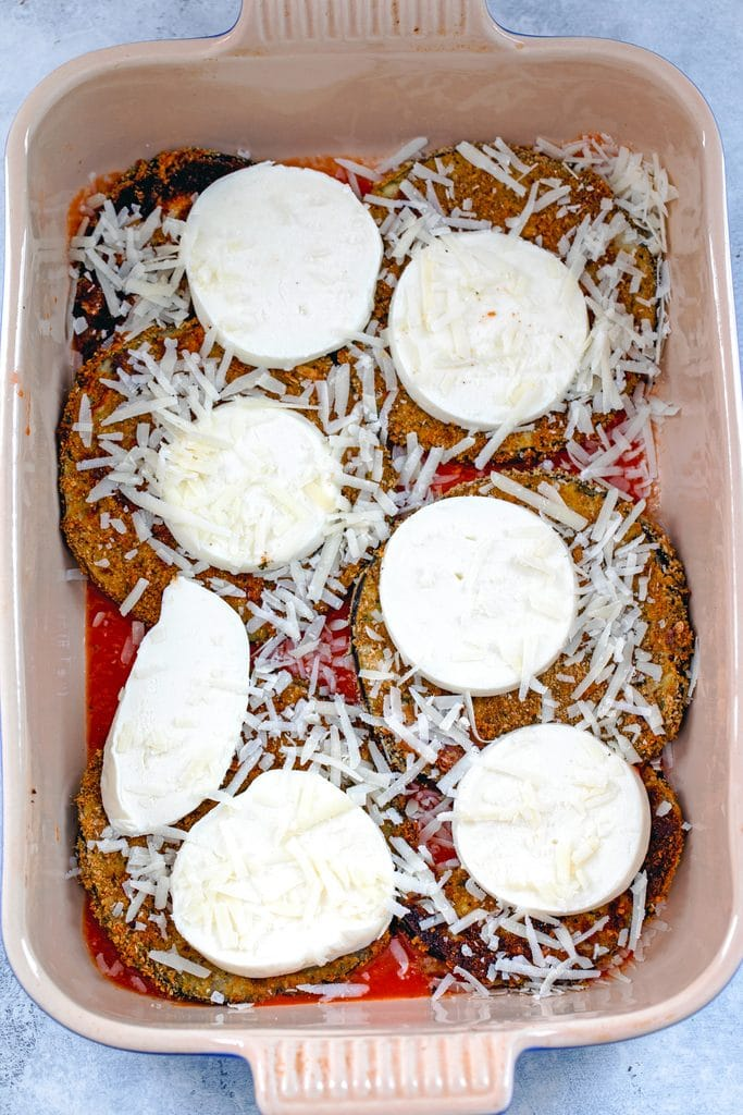 Overhead view of casserole dish with tomato sauce, eggplant, mozzarella, and parmesan cheese layered