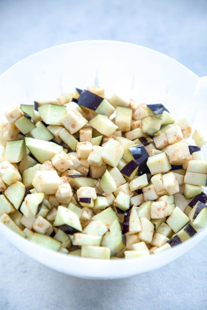 Overhead view of chopped eggplant in a colander