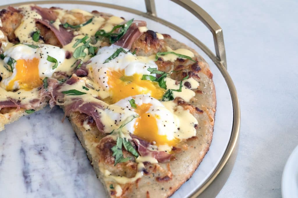 Landscape view of eggs benedict pizza on a marble tray with runny eggs, prosciutto, and hollandaise sauce over the top