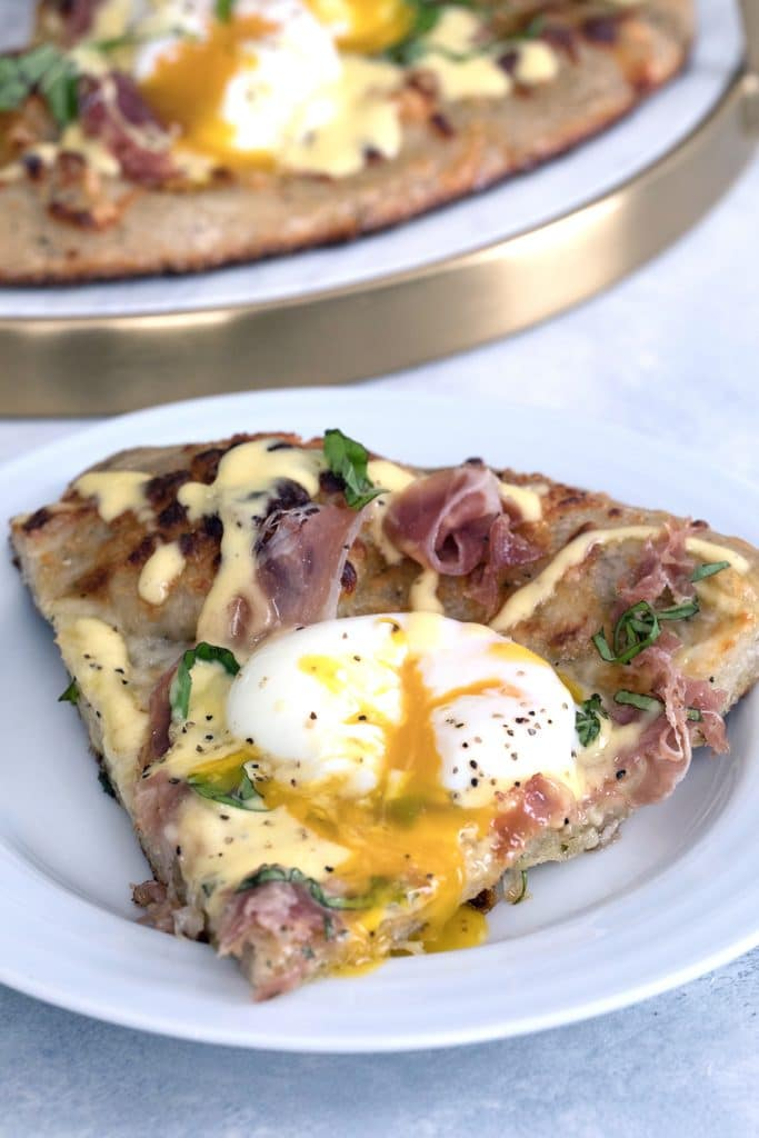 Head-on view of a slice of eggs benedict pizza on a white plate with runny egg, prosciutto, and hollandaise sauce