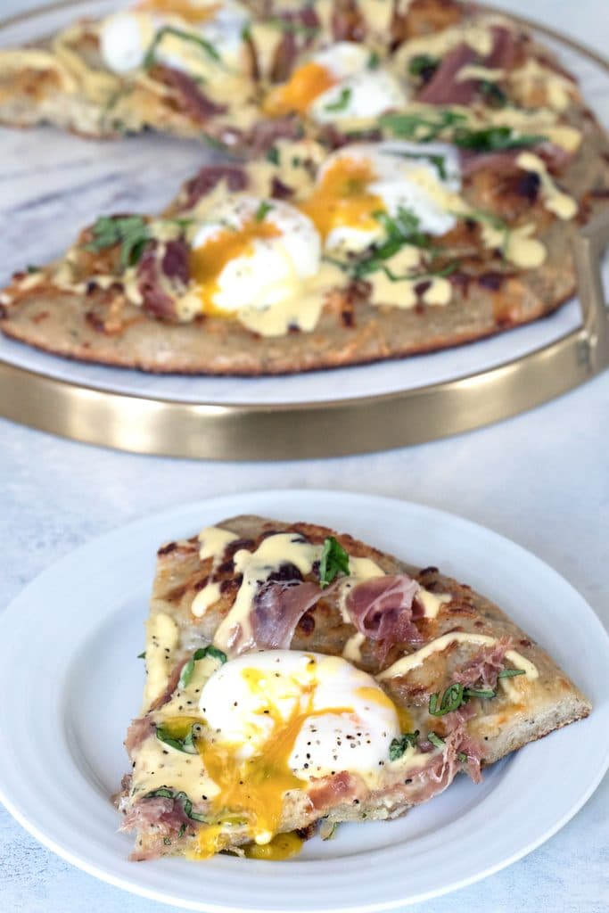 Overhead view of a slice of eggs benedict pizza with runny egg on a white plate with rest of brunch pizza in background