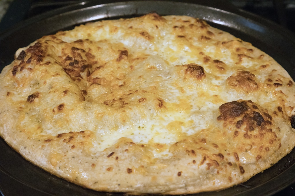 Pizza crust with cheeses just out of oven