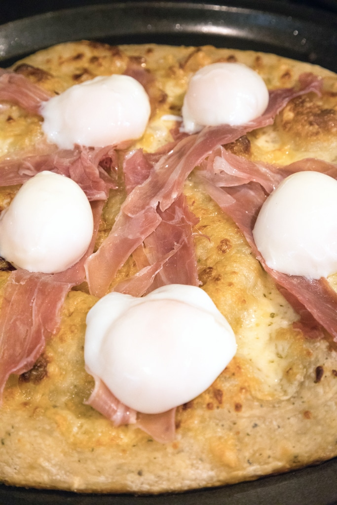 Sous vide eggs and prosciutto on top of pizza