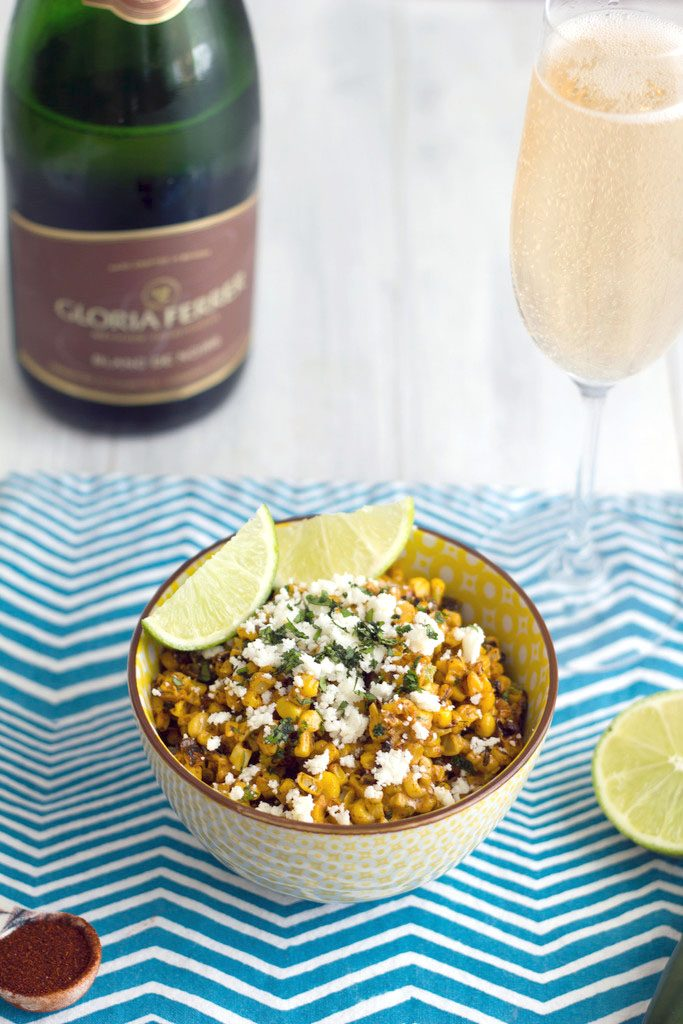 Head-on view of elote salad on a blue striped towel with lim garnish and bottle and glass of champagne in the background