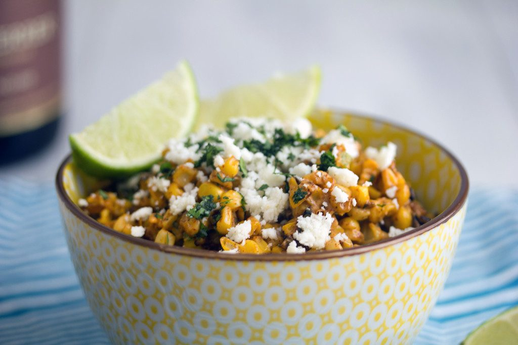 Landscape view of elote salad in yellow bowl topped with cotija cheese and lime wedges