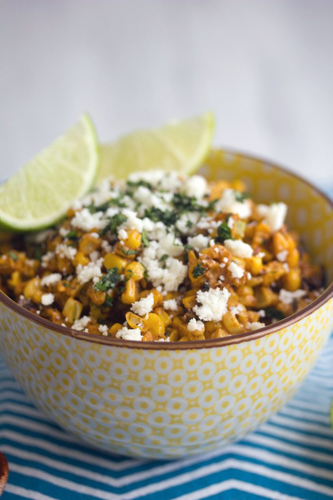 Close-up of elote salad in yellow bowl on blue zigzag placemat topped with cotija cheese and lime wedges
