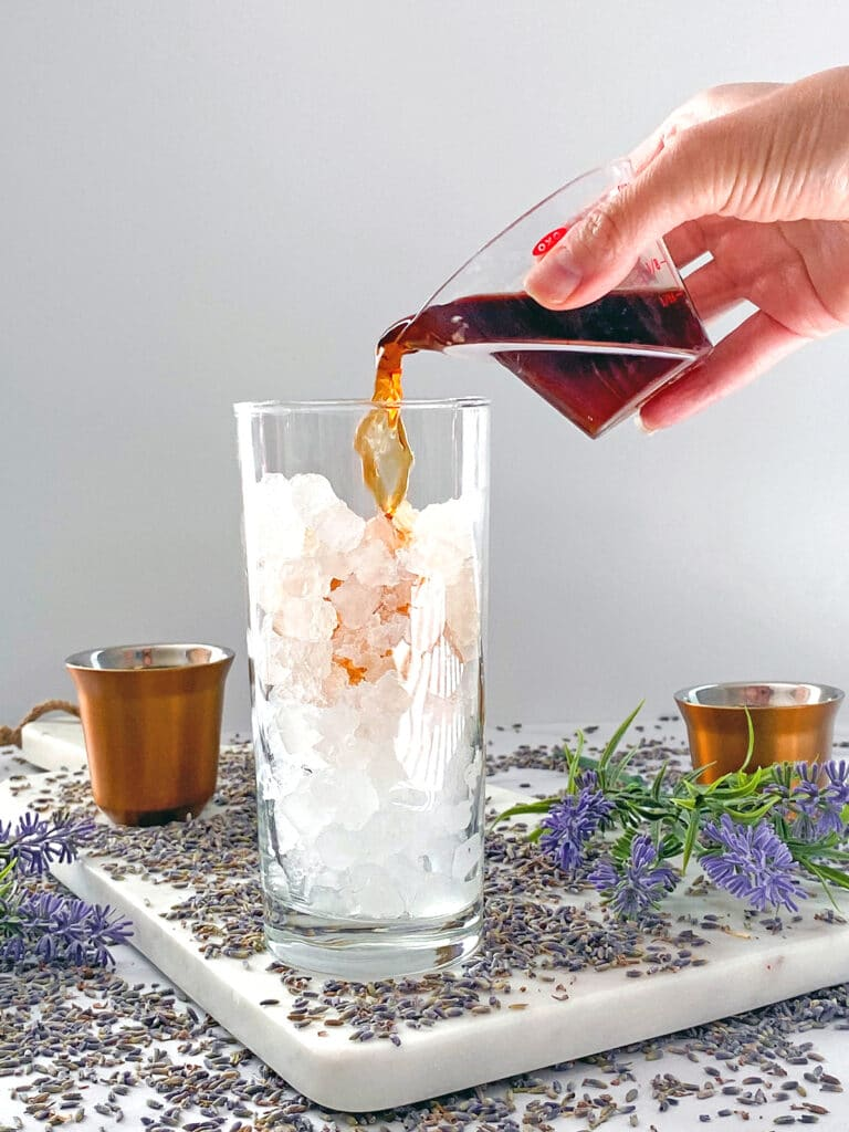 Espresso being poured into ice-filled glass with lavender flowers all around