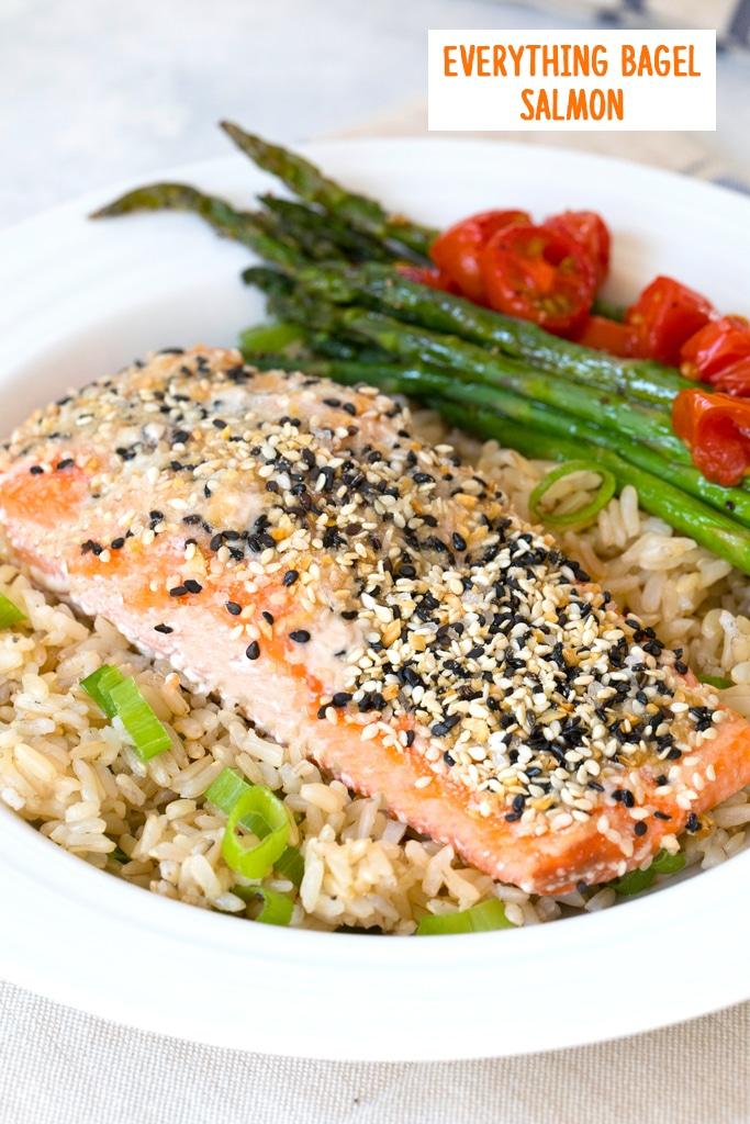 Head-on view of a piece of salmon coated with everything bagel spice over a bed of brown rice with asparagus  and grape tomatoes in the background and recipe title at top