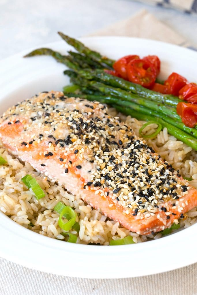 Head-on view of a piece of salmon coated with everything bagel spice over a bed of brown rice with asparagus  and grape tomatoes in the background.