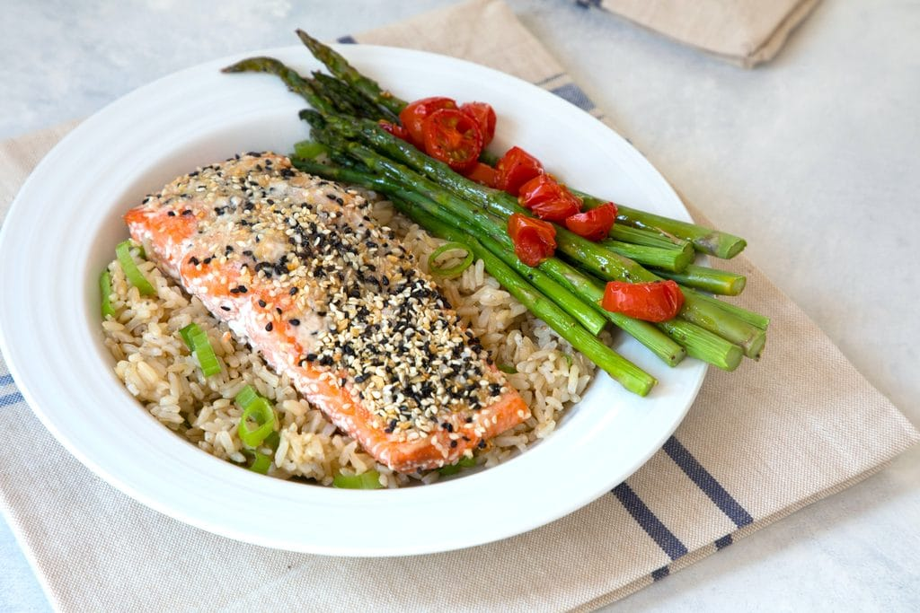 Landscape overhead view of a piece of salmon coated in everything bagel spice over a bed of brown rice with asparagus and grape tomatoes.