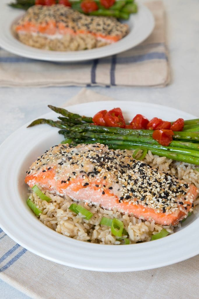 View from a distance of everything bagel salmon served over a bed of brown rice with asparagus and grape tomatoes.