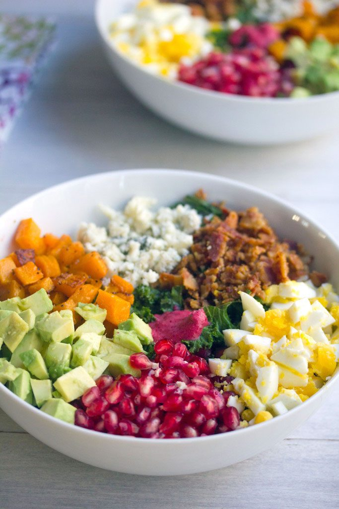 Head-on view of a fall cobb salad with kale, pomegranate, avocado, butternut squash, gorgonzola, bacon, and hardboiled egg with second bowl of salad in the background