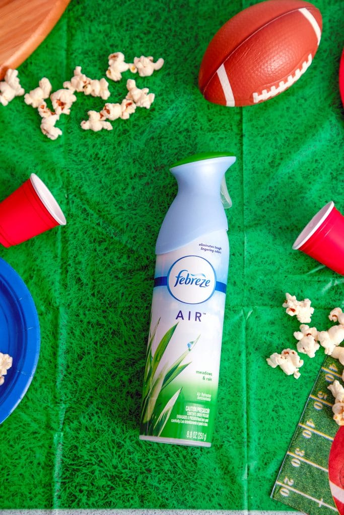 Bird's eye view of Febreze AIR on football field tablecloth with spilled popcorn, mini footballs, cups and plates
