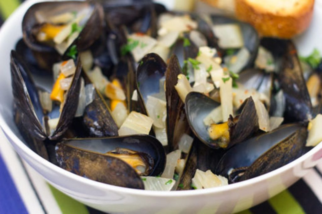 Landscape head-on closeup view of spicy fennel mussels in white bowl