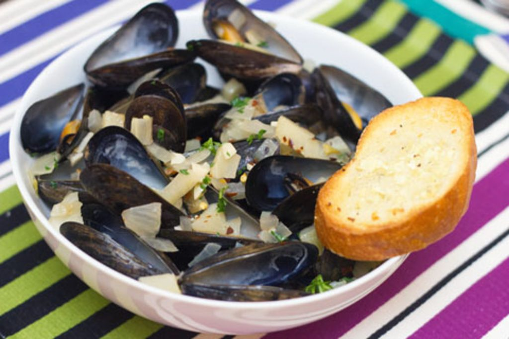 Head-on view of spicy fennel mussels in a white bowl with side of garlic bread on a colorful striped placemat