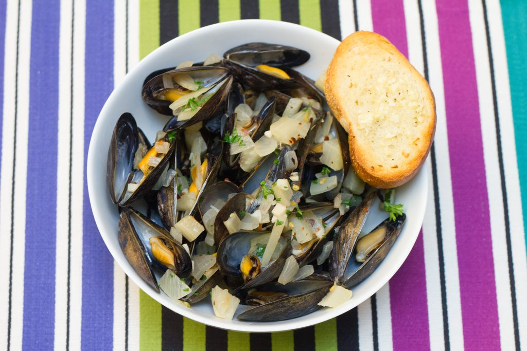 Overhead view of spicy fennel mussels in a white bowl with a side of garlic bread on a colorful striped placemat