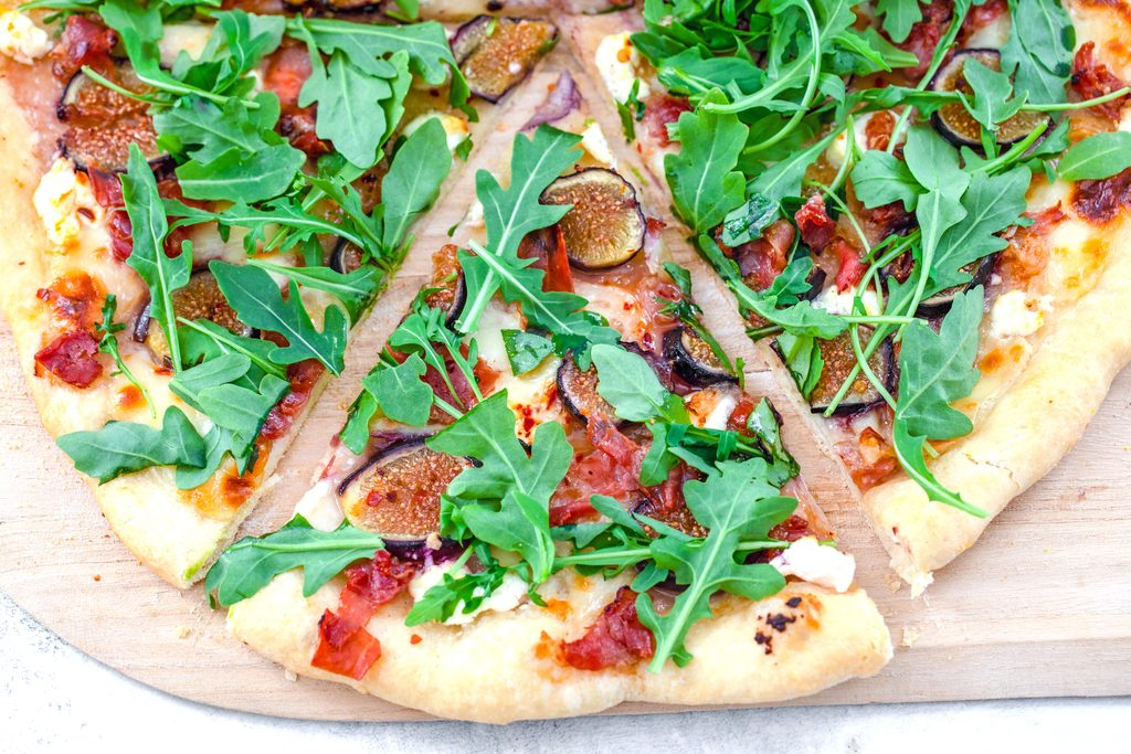 Landscape overhead closeup view of a slice of fig, prosciutto, and goat cheese flatbread topped with arugula