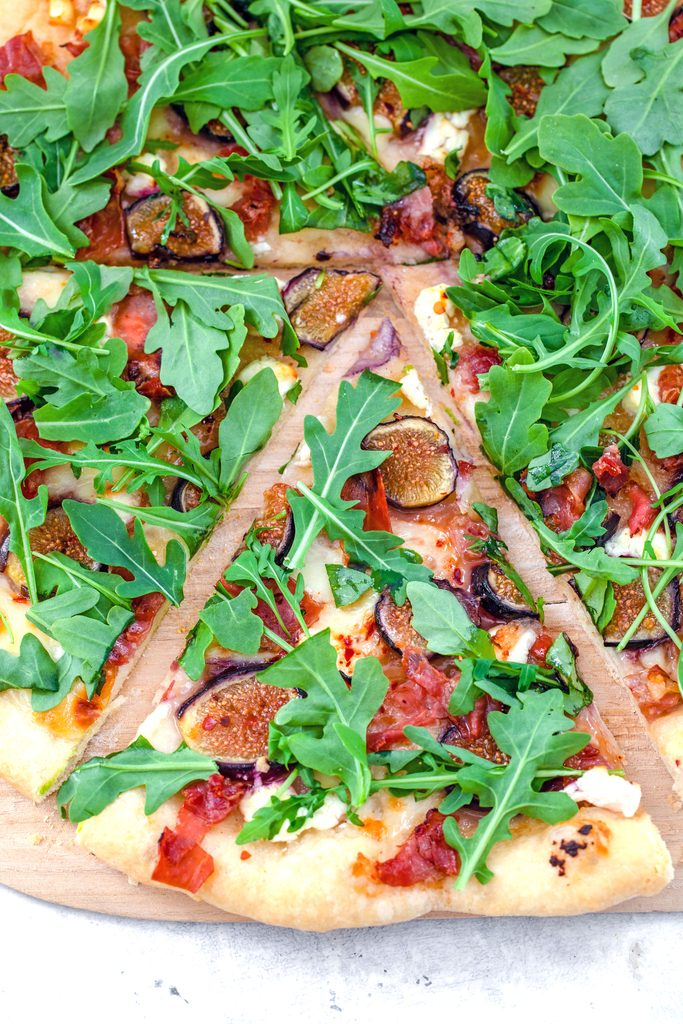 Overhead view of a slice of fig, prosciutto, and goat cheese flatbread topped with arugula and pulled out from the rest of the pizza
