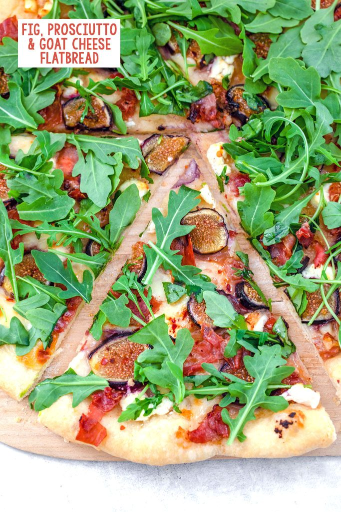 Overhead view of a slice of fig, prosciutto, and goat cheese flatbread topped with arugula and pulled out from the rest of the pizza with recipe title at top