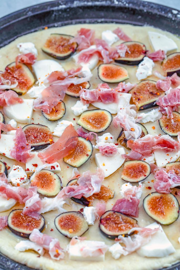 Overhead view of flatbread dough rolled out on pan and topped with sliced figs, prosciutto, goat cheese, and mozzarella