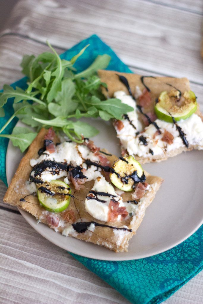 Overhead view of two slices of fig, prosciutto, and ricotta flatbread on a plate with arugula on the side