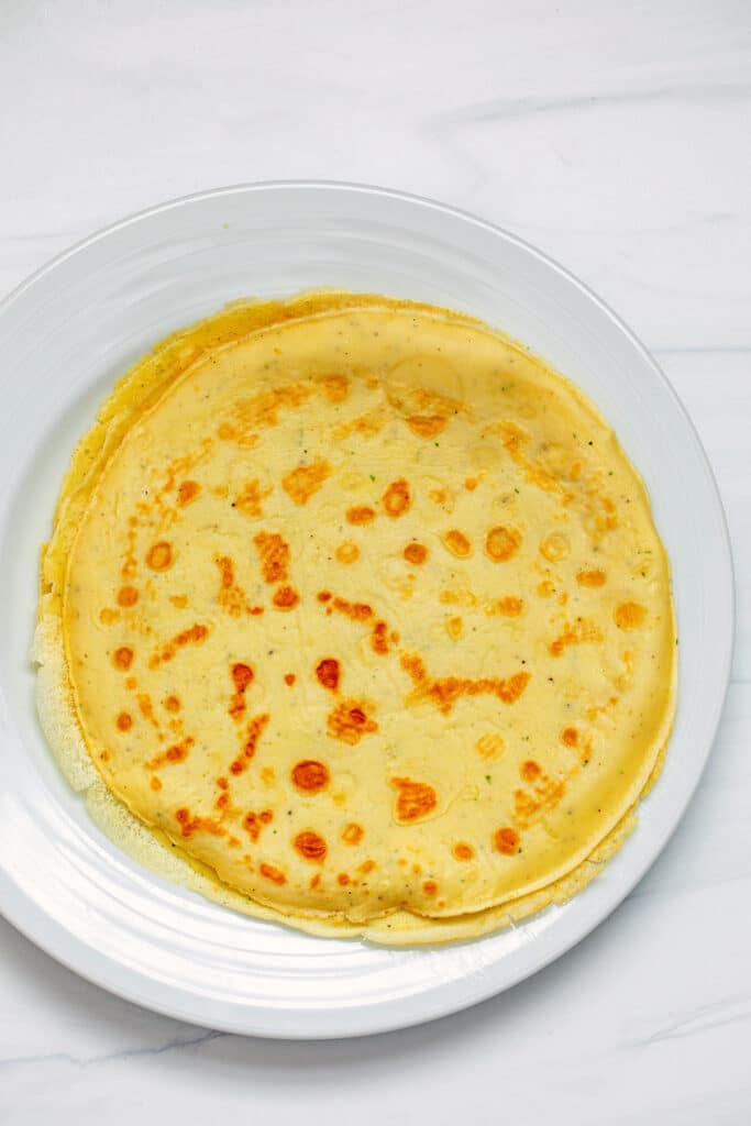 Overhead view of finished crepes on a plate
