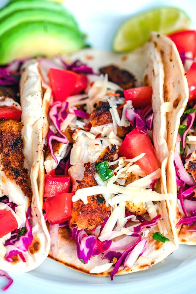 Head-on close up view of a fish taco topped with shredded cheese, tomatoes, and red cabbage with sliced avocado and lime wedge in the background