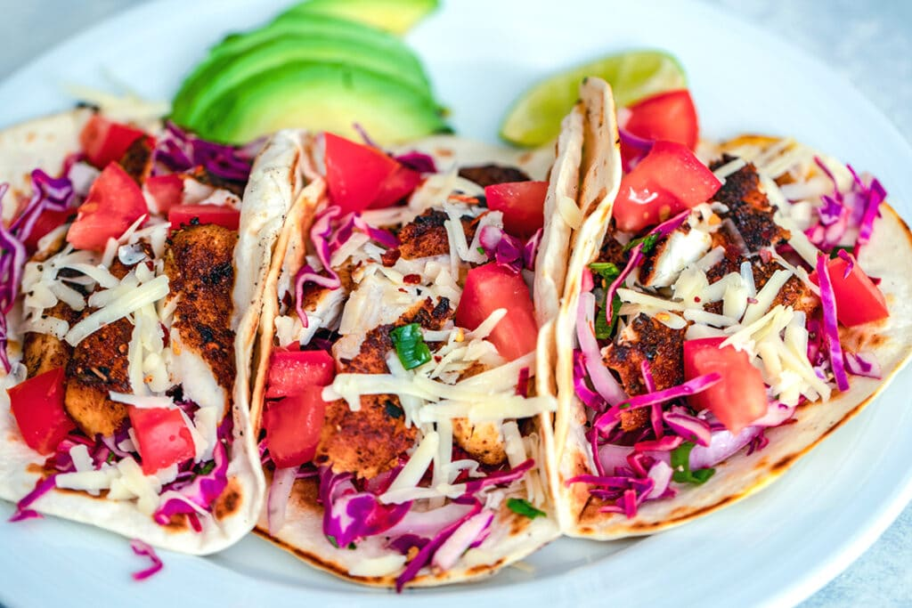 Landscape head-on view of three fish tacos on a white plate topped with red cabbage, tomatoes, and shredded cheese with sliced avocado and a lime wedge in the background