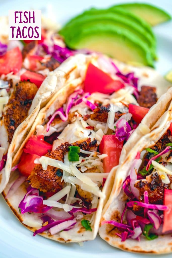 "Close-up for fish tacos with bright purple cabbage, red tomatoes, and shredded cheese with sliced avocados in the background and ""Fish Tacos"" text at the top of the photo"