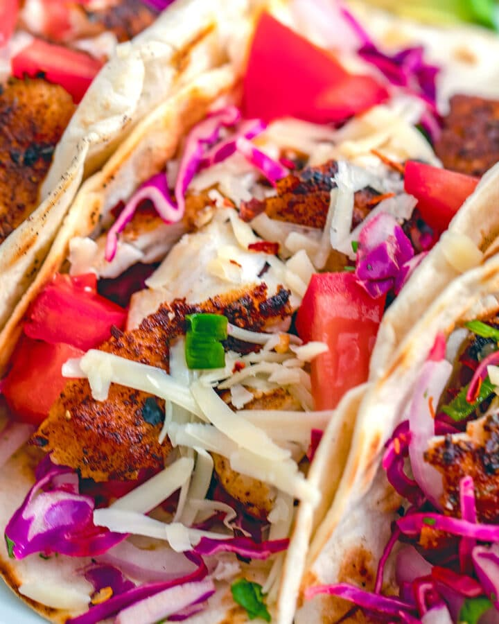 Closeup view of a fish taco topped with cheese, tomatoes, and red onion and cabbage slaw