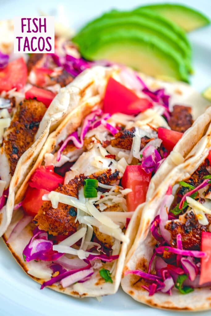 """Close-up for fish tacos with bright purple cabbage, red tomatoes, and shredded cheese with sliced avocados in the background and """"Fish Tacos"""" text at the top of the photo"""