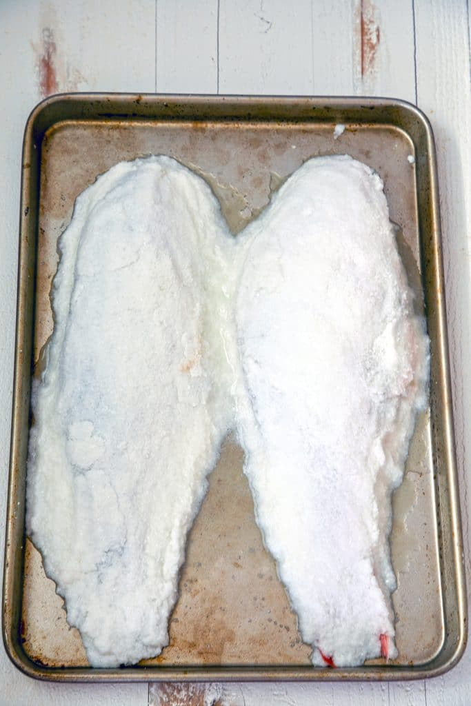 Overhead view of baking pan with two salt-covered whole fish before baking
