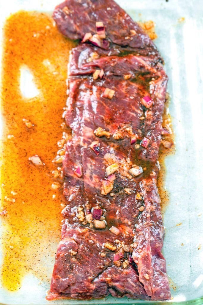 Overhead view of flank steak/skirt steak marinating in a baking dish