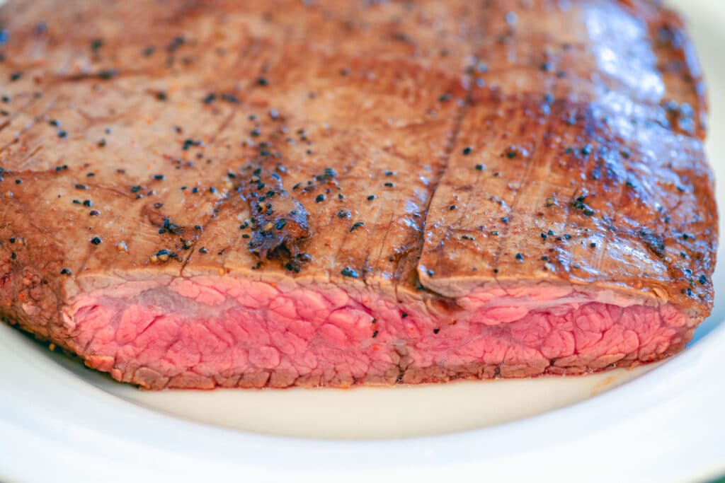 View of flank steak cooked rare with slice taken out