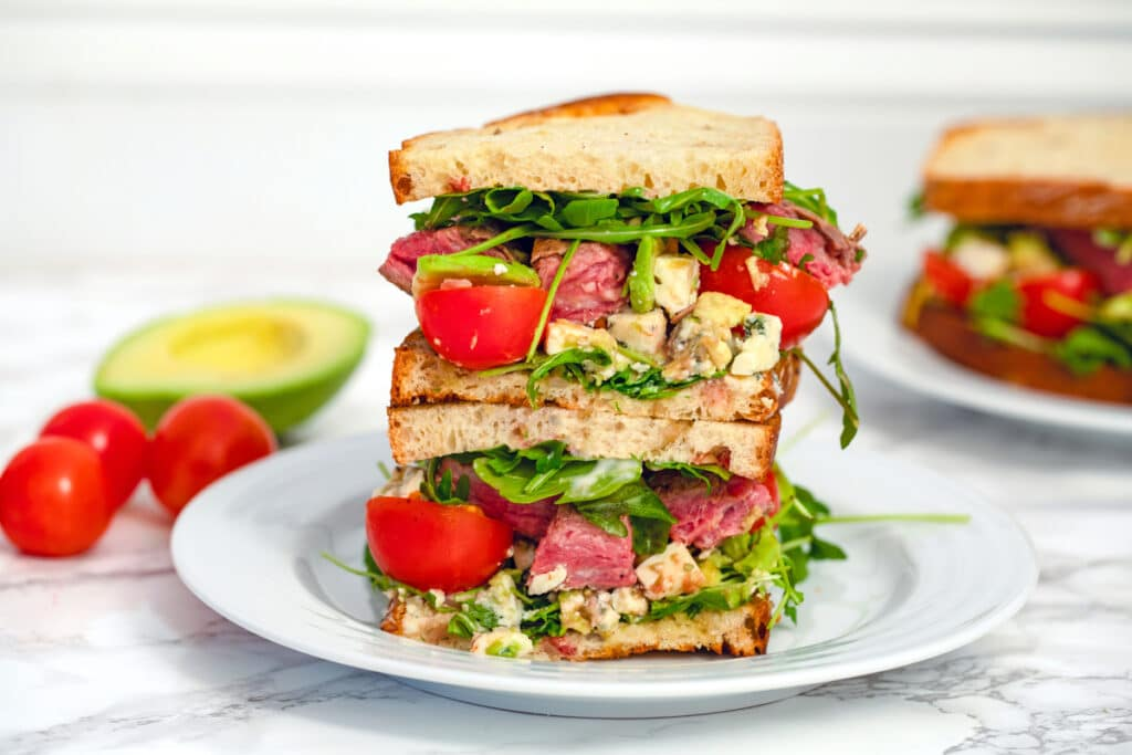 Landscape head-on view of two halves of a flank steak sandwich stacked on top of each other with avocado and tomatoes and second sandwich in the background