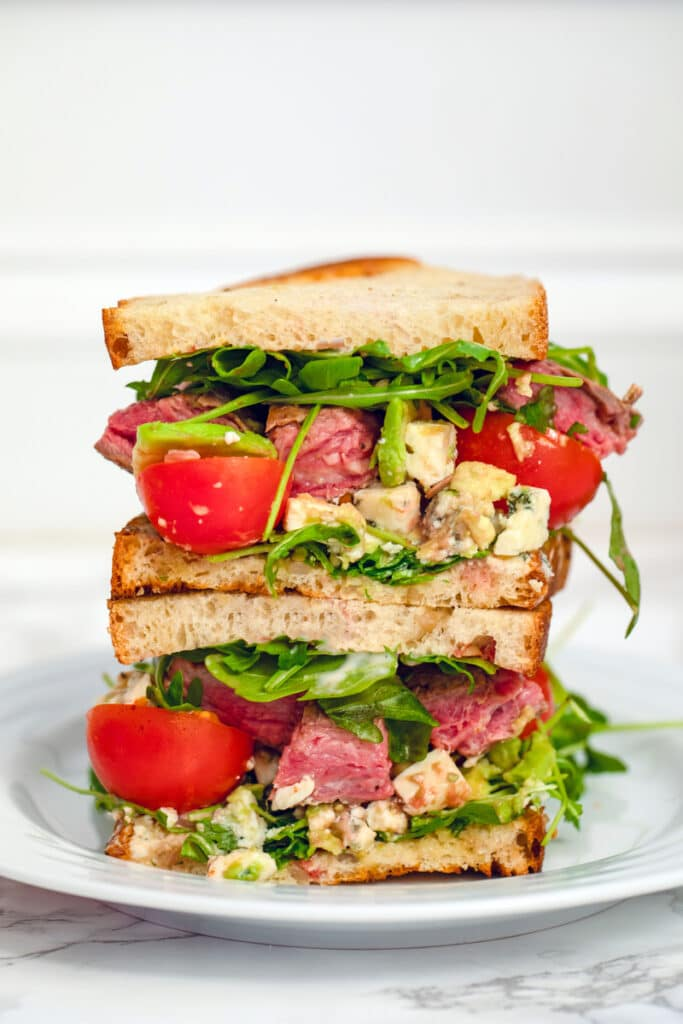 Head-on close-up view of two halves of a flank steak sandwich stacked on top of each other with steak, arugula, tomatoes, avocado, and gorgonzola