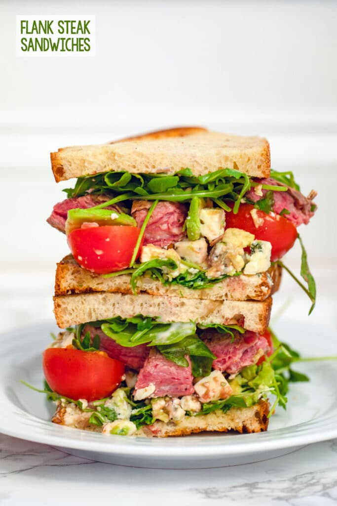 Head-on close-up view of two halves of a flank steak sandwich stacked on top of each other with steak, arugula, tomatoes, avocado, and gorgonzola with recipe title at top