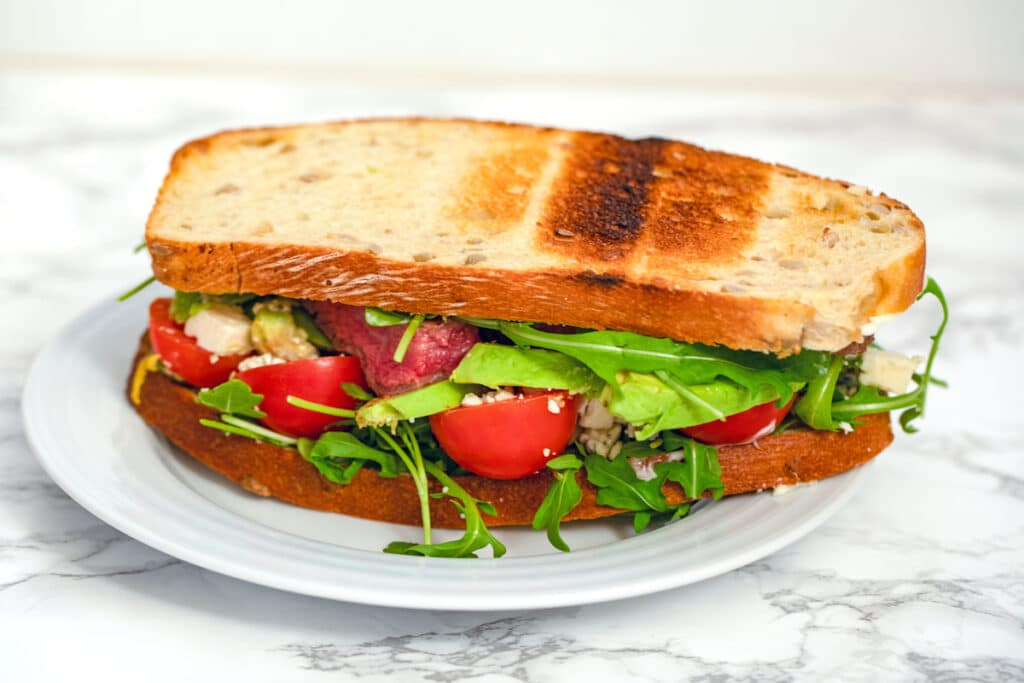Head-on view of a flank steak sandwich with arugula, tomatoes, avocado, and gorgonzola