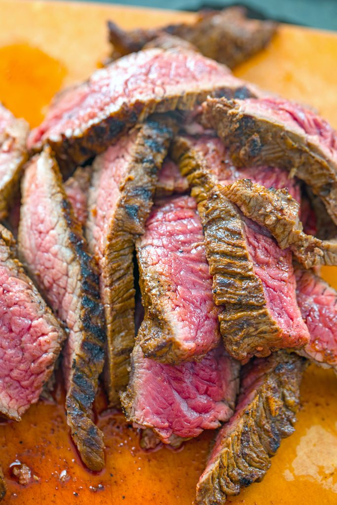 Overhead view of thinly sliced flank steak on cutting board