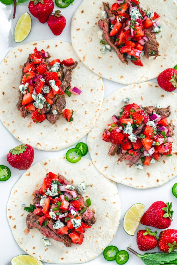 Overhead flat-lay view of multiple flank steak tacos topped with strawberry mint salsa and gorgonzola cheese with strawberries, mint, lime wedges, and jalapeño slices all around