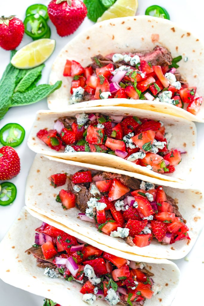 Overhead view of four flank steak tacos with strawberry mint salsa and gorgonzola cheese with mint, strawberries, lime wedges, and jalapeño slices in the background