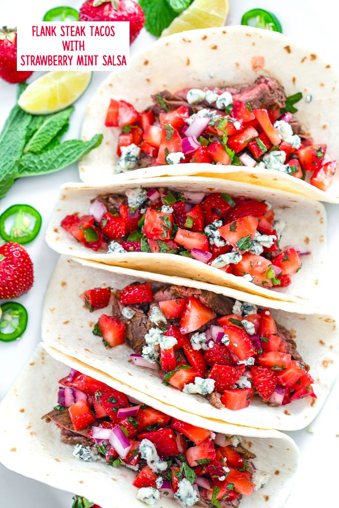 Overhead view of four flank steak tacos with strawberry mint salsa and gorgonzola cheese with mint, strawberries, lime wedges, and jalapeño slices in the background with recipe title at top