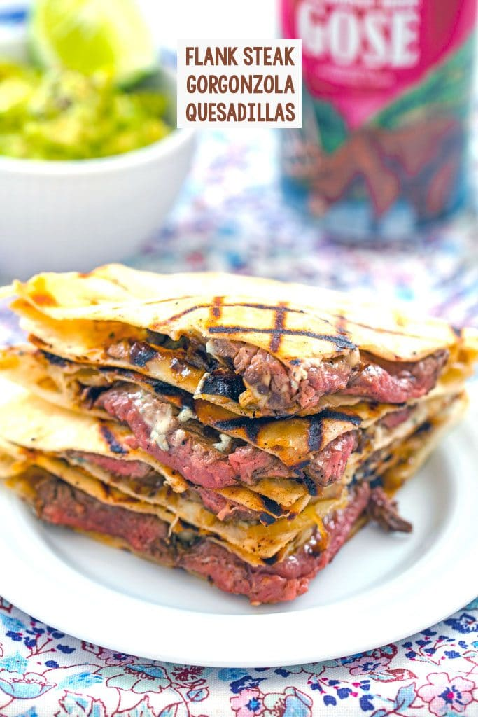 Head-on view of flank steak quesadillas with gorgonzola stacked on each other with bowl of mashed avocado and beer can in the background and recipe title at top