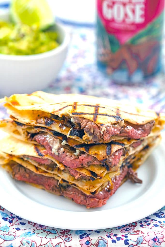 Head-on view of flank steak quesadillas with gorgonzola stacked on each other with bowl of mashed avocado and beer can in the background