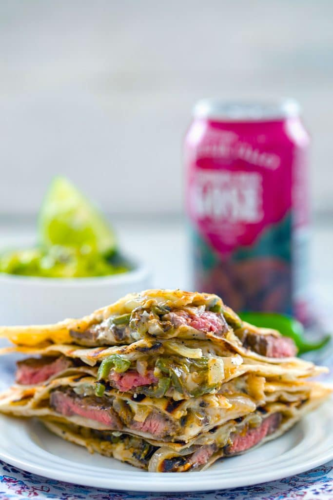 Straight-on view of sliced flank steak quesadillas stacked on top of each other with onions, jalapeño peppers, and gorgonzola cheese with bowl of mashed avocado and beer can in the background