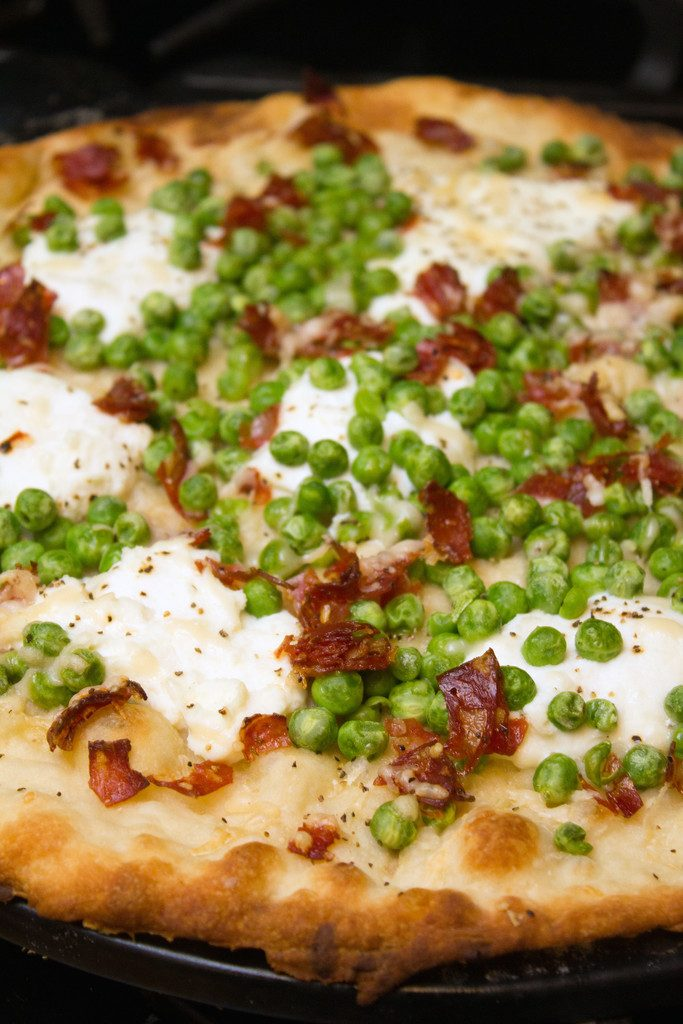 Lemon parmesan spring flatbread topped with ricotta, peas, and capicola just out of the oven