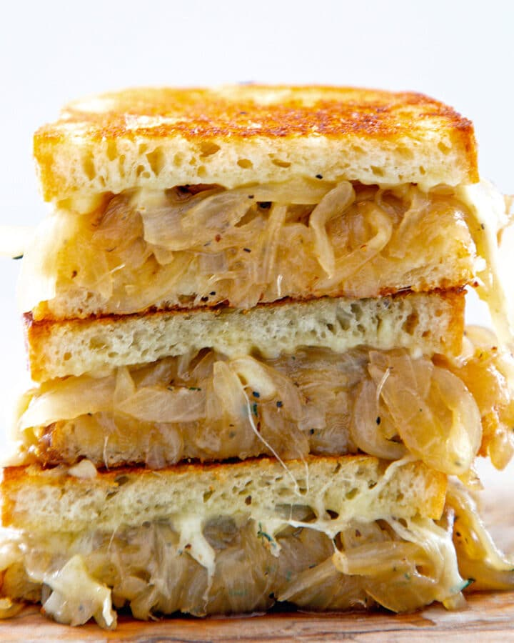 Closeup view of three halves of a french onion grilled cheese sandwich stacked on each other