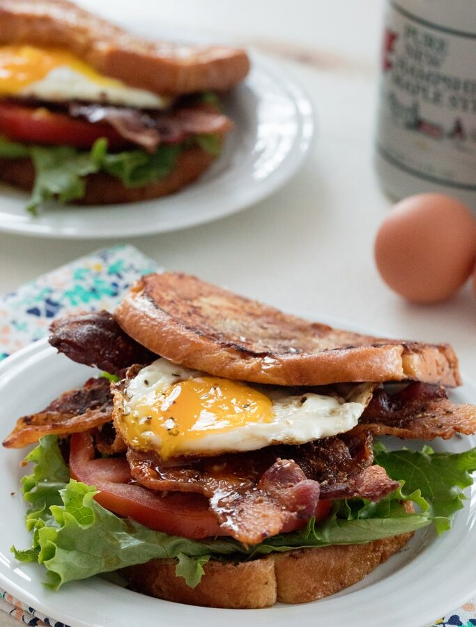 French Toast BLTs -- This breakfast sandwich will give you a reason to get out of bed in the morning! Made with challah or brioche french toast, crispy bacon, lettuce, tomato, and a fried egg, be sure to drizzle plenty of maple syrup over the top before serving | wearenotmartha.com